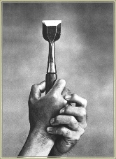 Hands holding a chisel used in piano making